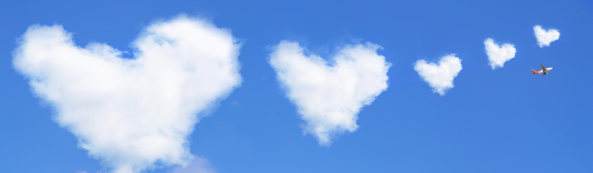 Airplane amidst heart shaped clouds