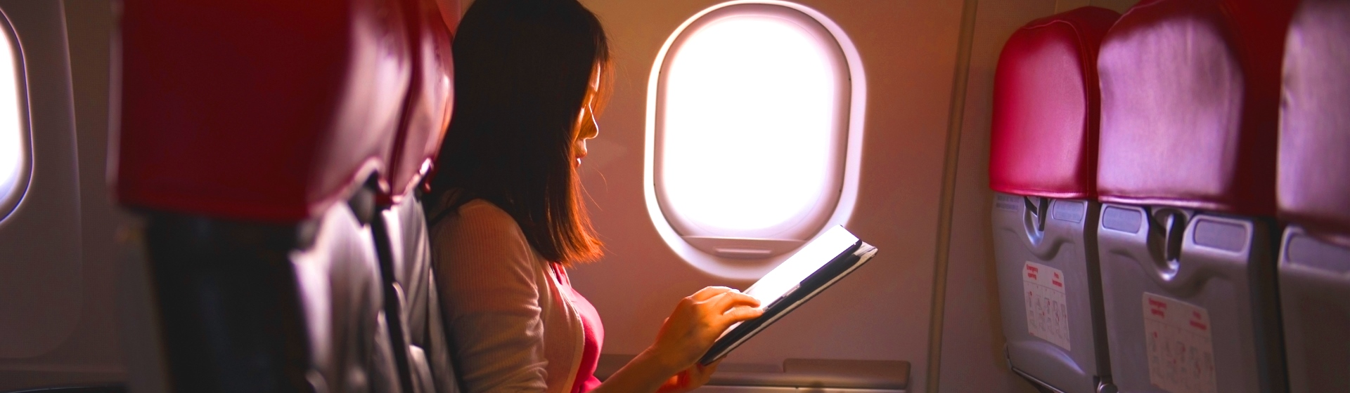 Woman on a plane using her tablet.