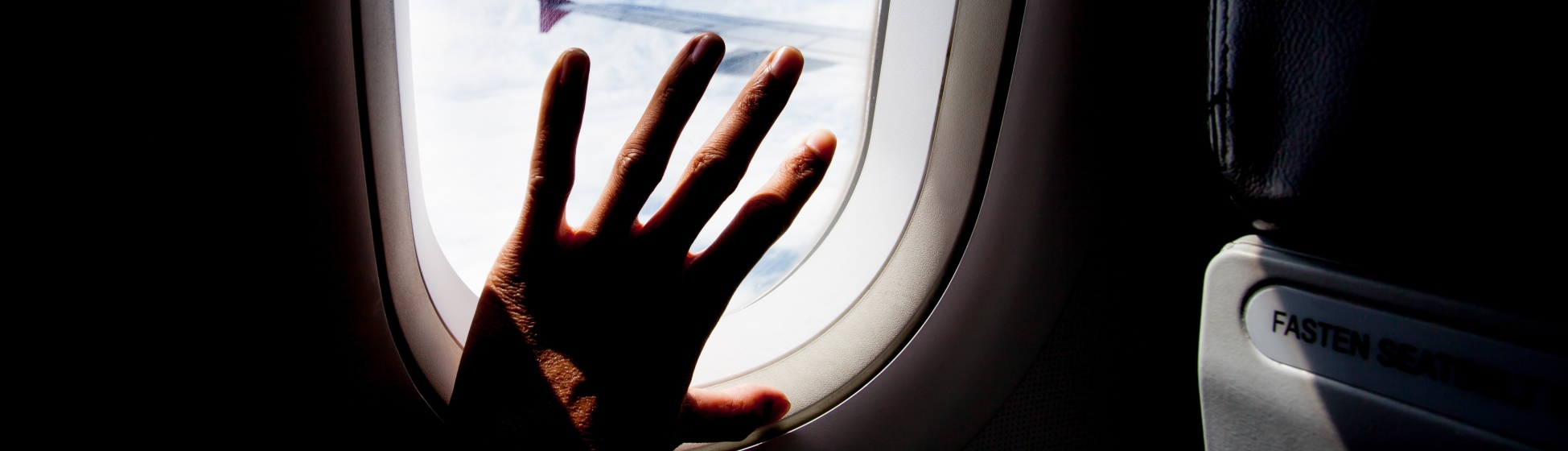 Hand on plane window